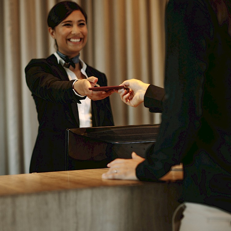 woman hotel clerk giving out a key